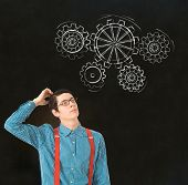 picture of geek  - Nerd geek businessman student or teacher with chalk thinking turning gear cogs or gears on blackboard background - JPG