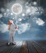 stock photo of moonlight  - Young little girl playing at night with a balloon moon on a string with stars in the blue sky with clouds for a dream concept - JPG