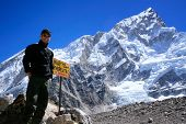 Man standing next to signpost to the Mount Everest Base Camp with Nuptse mountain in the background,