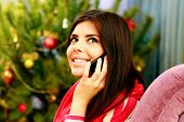 Young happy thoughtful woman talking on the phone and looking up at home