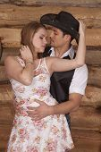 foto of sweethearts  - A couple is standing in front of a wood background looking at each other - JPG