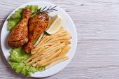 Two Fried Chicken Drumsticks With French Fries.  Top View