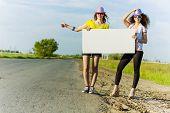 Zwei hübsche junge Mädchen beiseite Straße mit leeren weißen banner