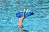 Paradox - Hand aus Wasser mit blauen Plastikflasche Wasser erhöhen