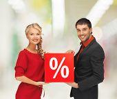 conceito de venda, compras e shopping - sorrindo, homem e mulher com o sinal de porcentagem em shopping center