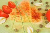 food : cheese casserole piece on green plate served with capers and tomatoes isolated over white