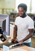 African American male librarian working at counter in bookstore