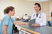 stock photo of reception-area  - Mature doctor and nurse looking at each other while using digital tablet at hospital reception - JPG