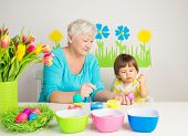 pic of grandma  - Loving grandma teaching her grandson to color eggs for Easter at home - JPG
