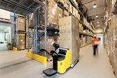 stock photo of warehouse  - Forklift with products in a huge warehouse - JPG