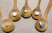 Pills with wooden spoon on wood background.