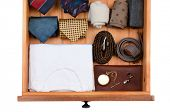 High angle shot of a dresser drawer with under shirts, belts, neck ties, socks, pocket watch and cuf