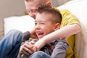 stock photo of tickle  - two little boys maybe friends or brothers two little boys laughing about tickling - JPG