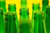 Ten Green Empty Beer Bottles Shot With Yellow Light. One Central Bottles In Focus.