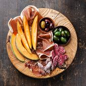 stock photo of antipasto  - Antipasto ham melon and olives on wooden background - JPG