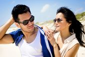 Portrait of a passionate young couple at the beach wearing sunglasses