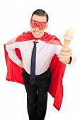 Man in superhero costume holding an ice cream isolated on white background
