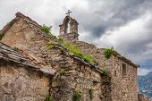 Stone old church under gloomy sky with clouds. Montenegro