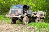 stock photo of logging truck  - Old wrecked truck loaded with logs in a forest - JPG