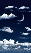 Surreal clouds in night sky with crescent moon