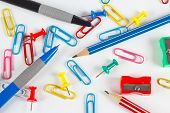 Pencil pen paperclips sharpeners and pushpins on white desktop