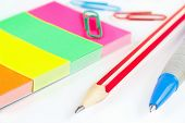 Multicolored school stationery on white desktop