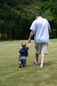 pic of father child  - Grandfather and grandson hold hands while walking - JPG