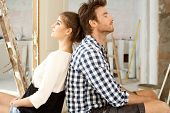 Young couple sitting on floor exhausted in renewing house. Sitting back to back.