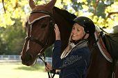 Outdoor portrait of female rider caressing horse.