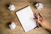 stock photo of messy  - Blank paper waiting for idea with hand and pen - JPG