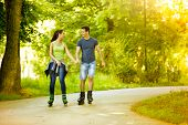 Young lovers in nature on rollerblades, enjoying in recreation
