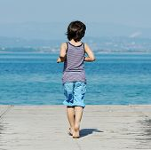 foto of dock a pond  - Little kid walking down the bridge on a sea summer dock - JPG