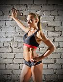 Muscular woman on grey brick wall background (normal version)