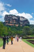 SIGIRIYA, SRI LANKA - 28 FEBRUARY, 2014: Tourists walking in garden complex with rock of Sigiriya as