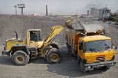 Yellow  Excavator Loads Gravel Into Orange Dumper Truck Tipper.