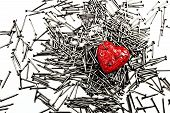 picture of love hurts  - Red love heart on pile of iron nails pierced by a three nails - JPG