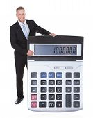Smilng Businessman Dsiplaying A Calculator