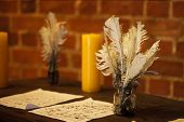 Feather Quill Pens Candle And Old Paper On Wooden Desk. Vintage.