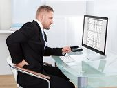 Businessman Rubbing His Back As He Sits Working At His Desk
