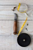 High angle shot of antique tools including a tape measure, carpet knife and tacks on a white washed