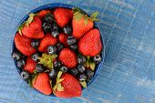 High angle shot of strawberries and blueberries in a blue enamelware bowl. The bowl is on a rustic w