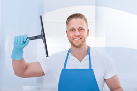 picture of disinfection  - Male janitor using a squeegee to clean a window in an office wearing an apron and gloves as he works - JPG