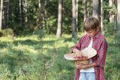 Teenage boy tasting fresh red wildberries