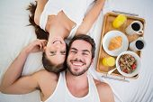 Young couple having breakfast in bed at home in bedroom