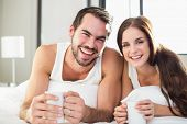 Young couple having coffee in bed at home in bedroom