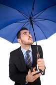Focused businessman under umbrella looking up on white background