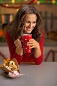 Happy Young Woman Drinking Cup Of Hot Chocolate With Christmas Cookies In Kitchen