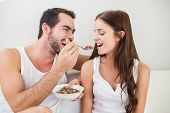 Young couple having breakfast in bed home in bedroom