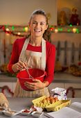 Portrait Of Smiling Young Housewife Whisking Dough In Christmas