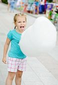 pic of candy cotton  - little girl eating  sweet cotton candy outdoors - JPG